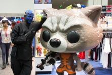 A sith snaps a picture with a Funko Rocket Raccoon statue.