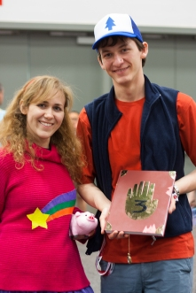 Mabel and Dipper of 'Gravity Falls' show off Waddles the Pig and the mysterious book of secrets.